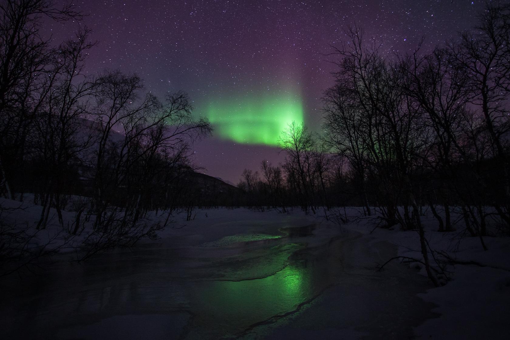 aurore boréale sur une rivière gelée dans les Alpes de Lyngen, en Norvège