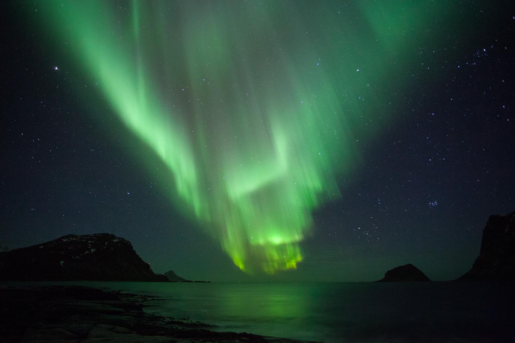 grande aurore boréale à la plage d'Haukland, dans les îles Lofoten