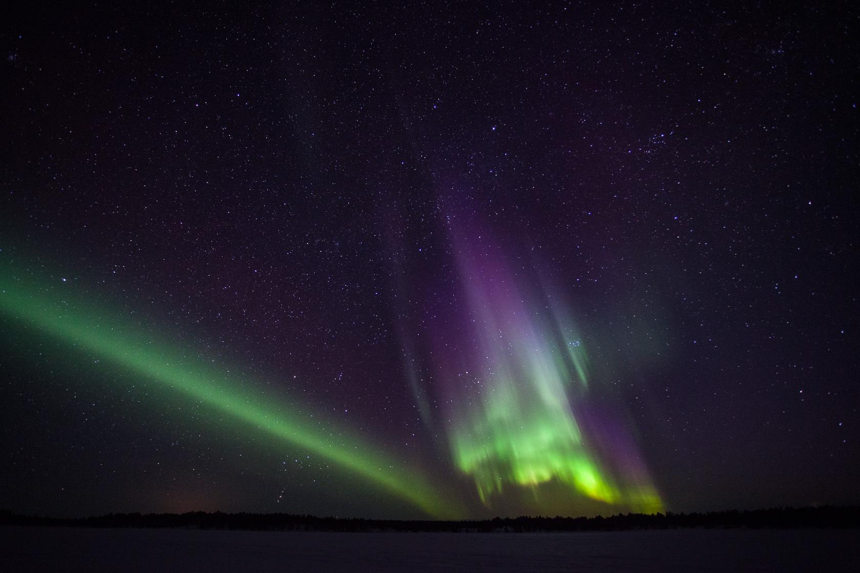 aurore boréale multicolore au dessus d'un lac gelé en Suède, à la frontière avec la Norvège