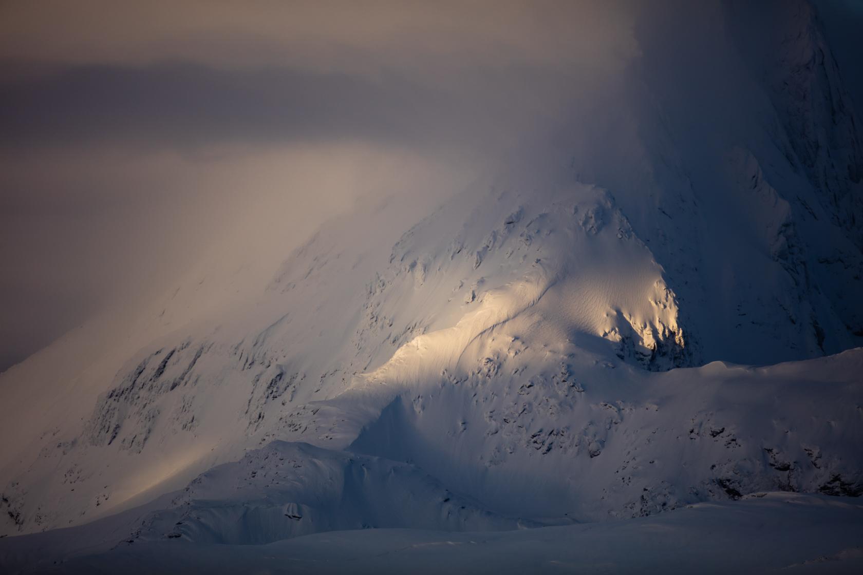 Raie de lumière sur une montagne enneigée, dans la région de Tromsø, en Norvège