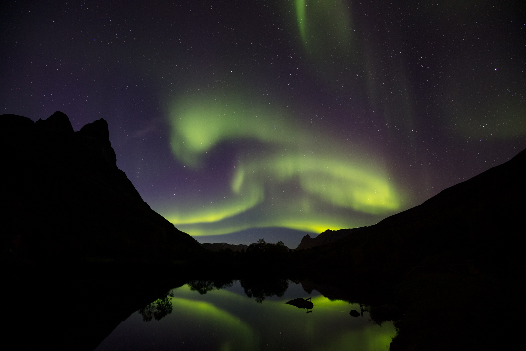 Aurores boréales et leurs reflets près de l'Otertinden, dans le région de Tromsø, en Norvège
