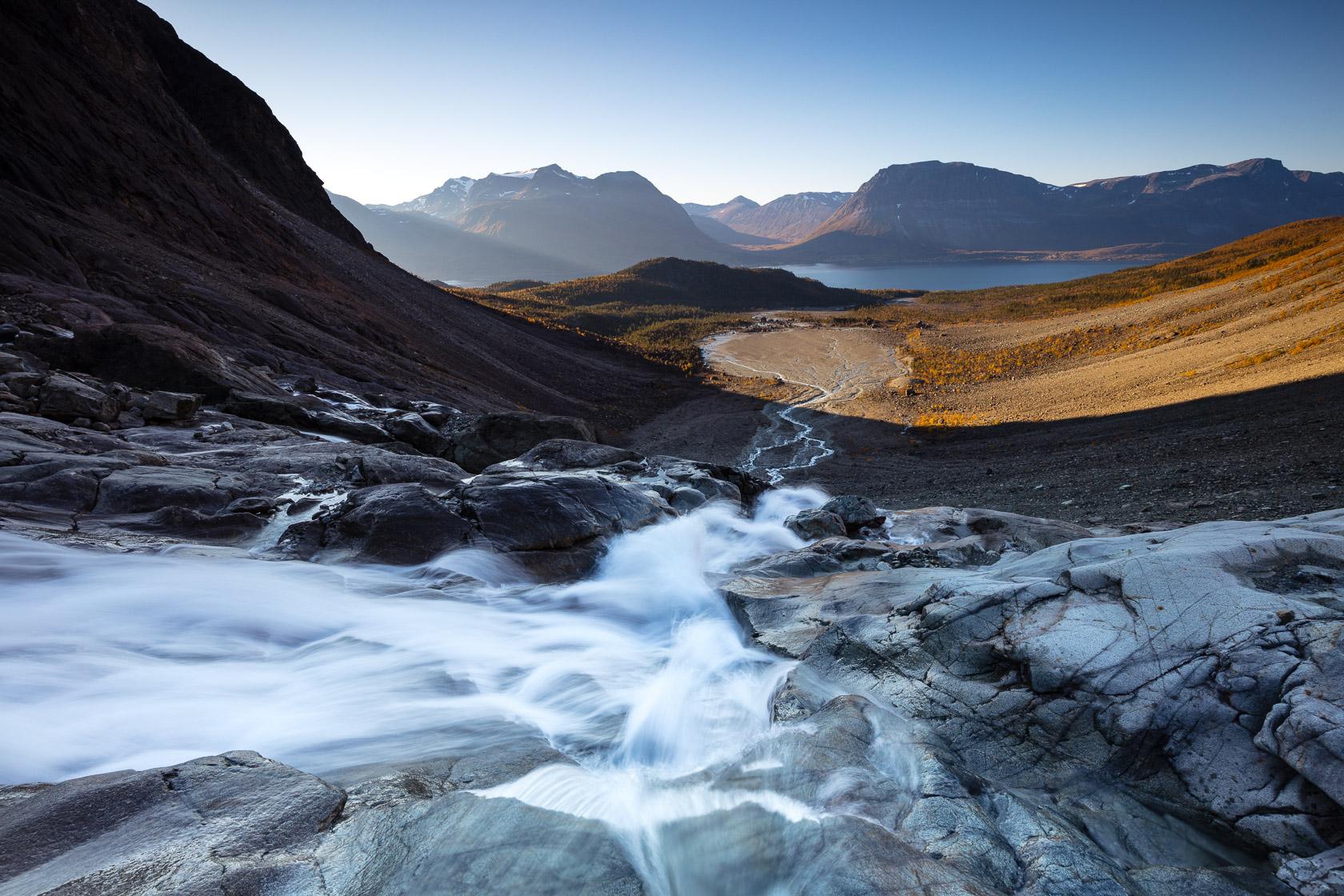 cascade dans les Alpes de Lyngen sur une vaste plaine de moraine glaciaire, en Norvège
