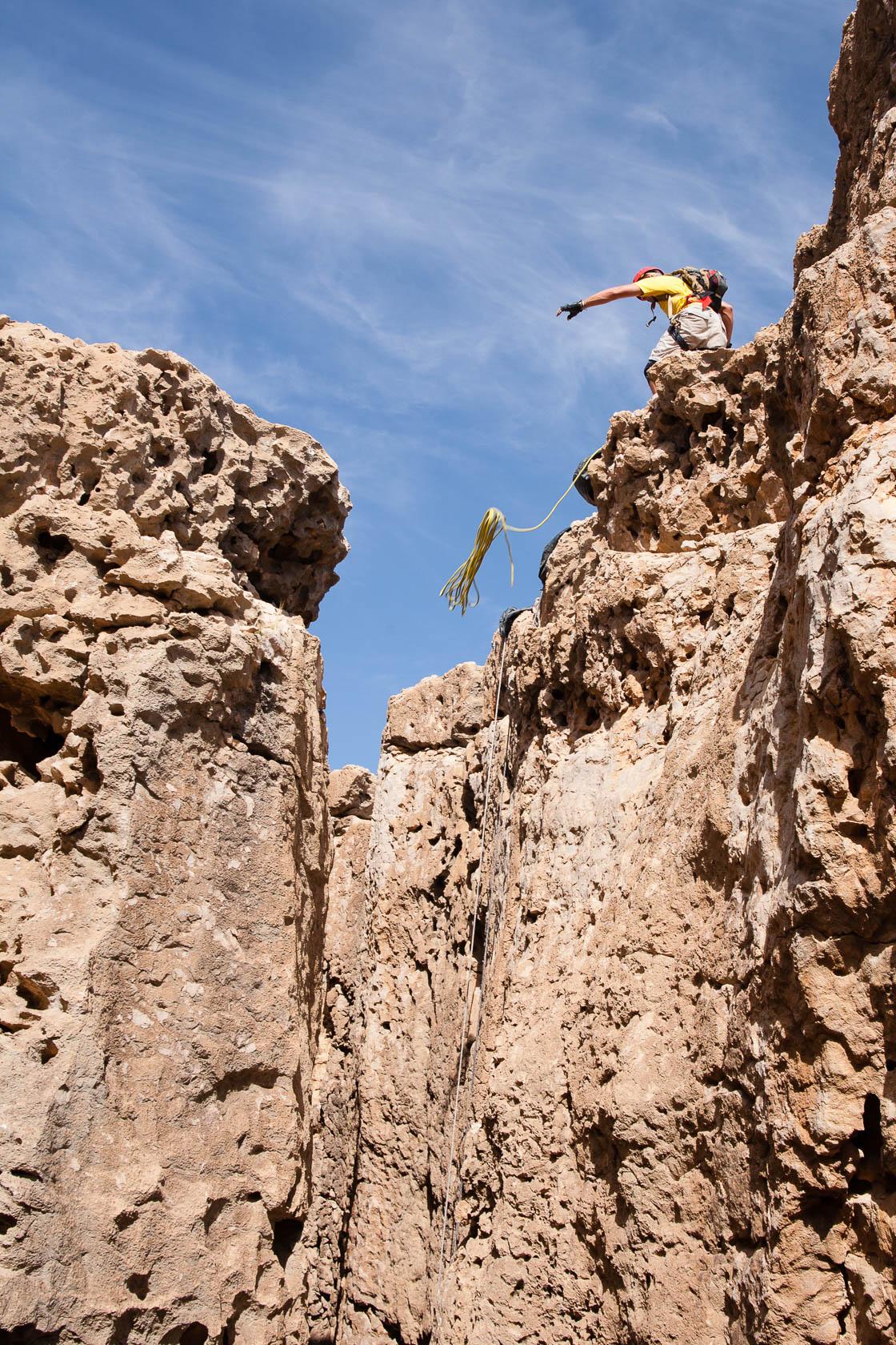 Justin lance la corde pour installer un rappel dans la grotte de Majilis Al Jins, sur le Salmah Plateau à Oman